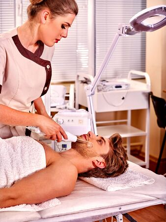 rf: Man receiving darsonval facial at beauty salon.