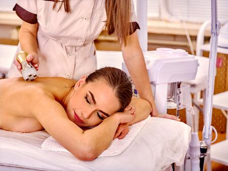 salon de belleza: Blanca muchacha que reciben masaje el�ctrica en el sal�n de belleza. En el fondo es un dispositivo para la cosmetolog�a hardware. Dos pepole.