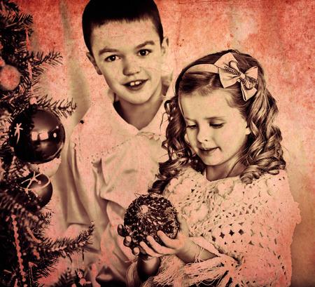 niños vistiendose: Niños hermana y decorar el árbol de navidad. Blanco y negro retro. Foto de archivo