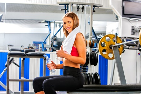 woman chest: Woman with towel working his arms and chest at gym. She relax near barbell. Stock Photo