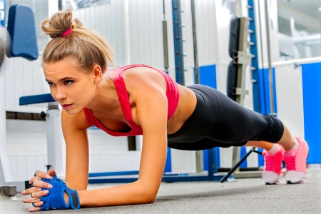 push ups: Young woman doing some push ups in gym.