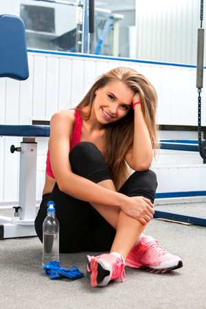 girl in sportswear: Fit woman sitting on the floor with bottle water at gym