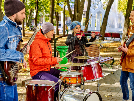 perform: Music street performers with girl violinist on autumn outdoor. Stock Photo