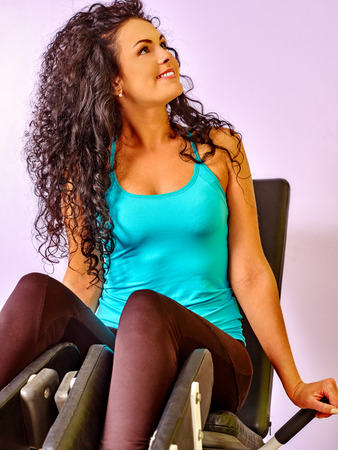 woman muscle: Girl workout on leg press in sport gym. Looking away.