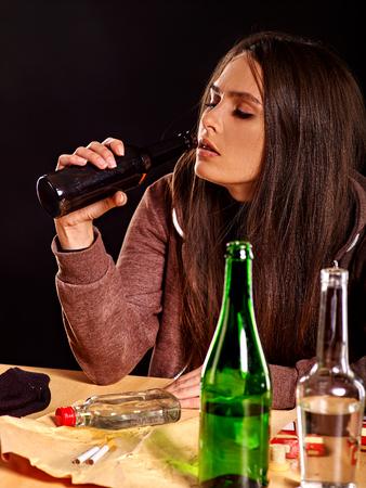 borracho: chica borracha con el pelo largo que sostiene la botella de alcohol. alcoholismo tema Soccial. Foto de archivo