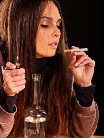 cigarette lighter: Young woman  smokes cigarette. Soccial issue smoking. Black background.