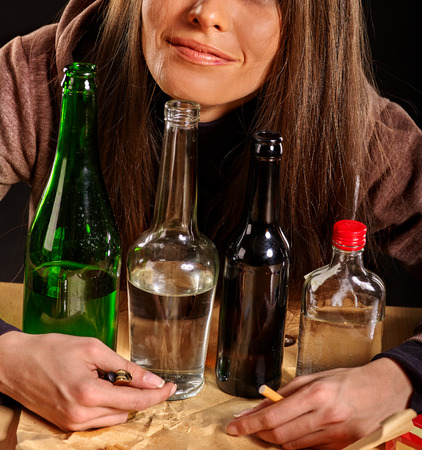 drinking alcohol: Young woman in depression drinking alcohol and smokes cigarettes in solitude. Stock Photo