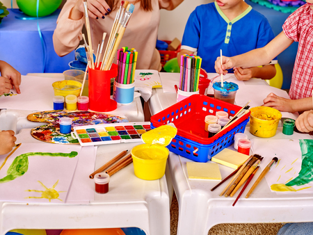 zábava: Skupina dětské ruce drží barevný papír a lepidlo na stole v mateřské škole.