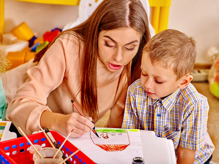 educator: Woman with kids holding colored paper and glue on table in kindergarten . Stock Photo