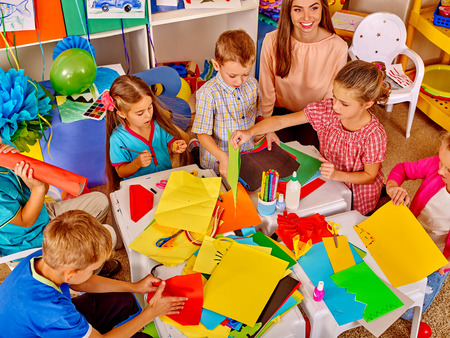 Group kids holding colored paper and glue on table in kindergarten . Top view.