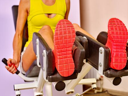 girl soles: Girl workout on leg press in sport gym. In the foreground soles of sneakers. Stock Photo