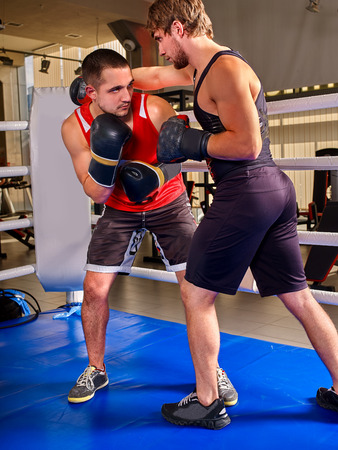 two men: Two  men boxer wearing helmet and  gloves boxing . Blue floor.
