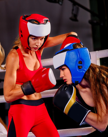 fight arena: Two  beautiful women boxer wearing red  gloves and helmet to box in ring.