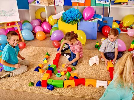 Group children game blocks on carpet floor in kindergarten . Top view.