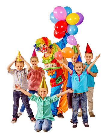 clown birthday: Clown holding cake and balloons on birthday with group children. Isolated. Stock Photo