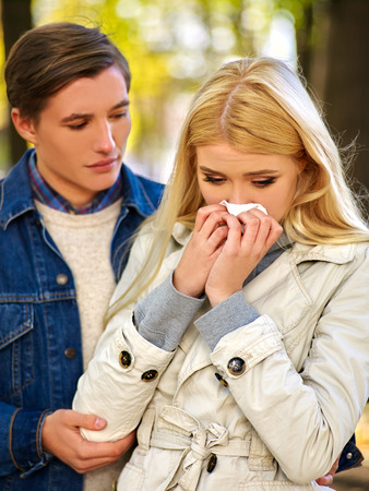 cold season: Woman with cold rhinitis on autumn outdoor. Fall flu season. Man looks with compassion on suffering of loved one. Stock Photo
