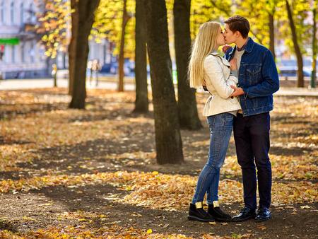 pareja abrazada: Pareja joven abrazos y coqueteando en el parque. Altura completa.