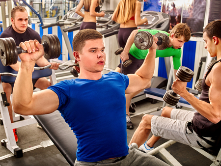 young guy: Group people and man in blue clothing working his arms and back at gym. He lying on bench and lifting barbell.