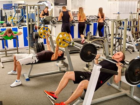 simulator: Group of people working on simulator his body at big gym.