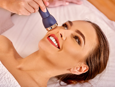 Young woman receiving electric facial massage at beauty  electroporation equipment. Stock Photo