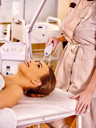 rf: Young woman receiving darsonval electric facial massage at beauty salon. Close up.