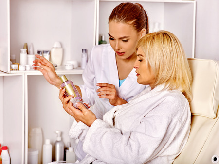 Woman 35-40 years old in spa salon with young beautician.