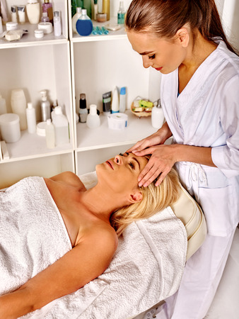 Woman middle-aged receiving face massage in spa salon with young beautician.