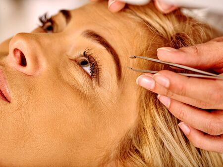 tweezing eyebrow: Woman middle-aged in spa salon with young beautician. Tweezing eyebrow by beautician.