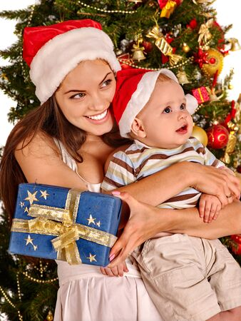 wearing santa hat: Mom wearing Santa hat holding  baby with blue and gold gift box  under Christmas tree.