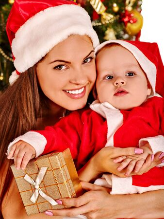 wearing santa hat: Mom wearing Santa hat holding  baby boy with gift box  under Christmas tree.