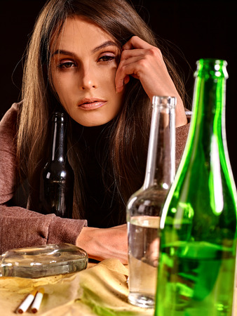 drunk girl: Drunk girl sitting near bottle of alcohol. Soccial issue alcoholism.