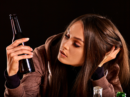 Drunk girl looking at bottle of alcohol. Soccial issue alcoholism. Stock Photo