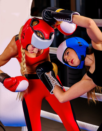 showgirl: Two  women boxer wearing red  gloves and helmet to box in ring. Martial arts.