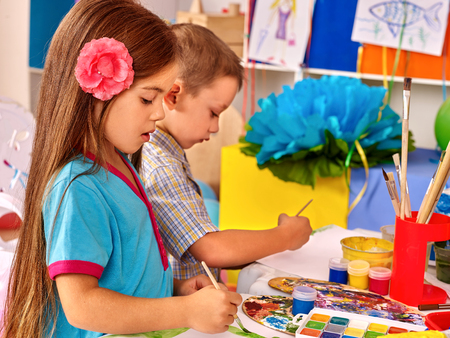 GUARDERIA: Los ni�os del grupo con la pintura del cepillo en la mesa en el jard�n de infantes.