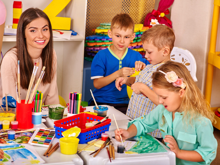 kinder: niños felices del grupo y mujer con la pintura del cepillo sobre la mesa en el jardín de infantes. Foto de archivo