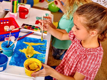 ni�os pintando: Grupo de ni�a con la pintura del cepillo en la mesa en el jard�n de infantes. Vista superior.