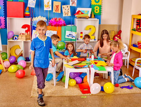 preschool teacher: Group kids in preschool interior holding colored paper and glue on table  .