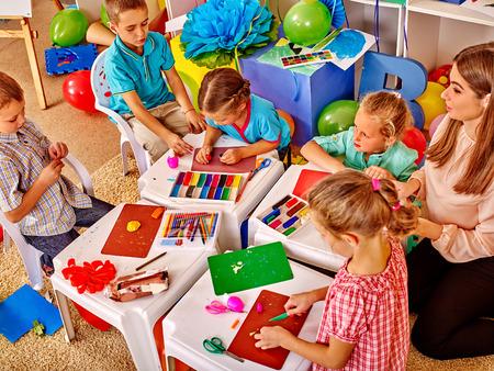 maestra preescolar: Grupo de niña y niños sosteniendo papel de colores y pegamento sobre la mesa en el jardín de infantes. Foto de archivo