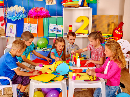 Group kids learning and holding colored paper and glue on table in kindergarten .