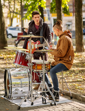 perform: Two Music street men performers on autumn outdoor.