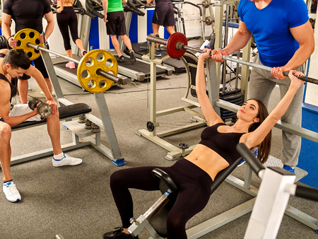 heavy lifting: Woman working his arms and chest at gym. She lifting barbell. Man help her.
