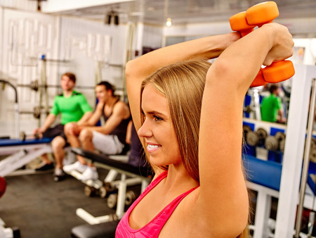 smilling: Smilling girls lift dumbbells in sport gym. Stock Photo