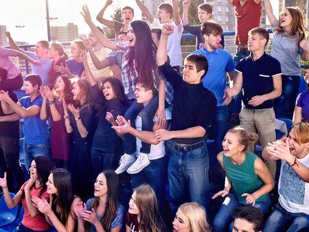 Les amateurs de sport applaudissant et chantant sur tribuns. Très grandes personnes Groupe.