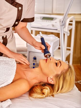 ultrasonic: Young woman receiving electric ultrasonic facial massage at beauty salon. Hardware cosmetology. Stock Photo