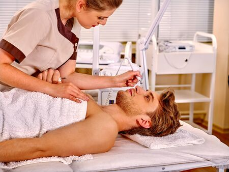 sound therapist: Man receiving electric facial hydradermie at beauty salon. Stock Photo