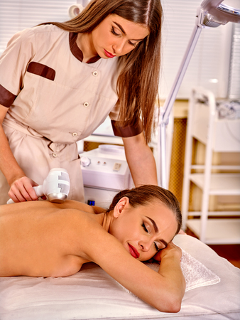 sound therapist: Young white  woman  receiving electric microdermabrasion massage at beauty salon. In room is device for hardware cosmetology.