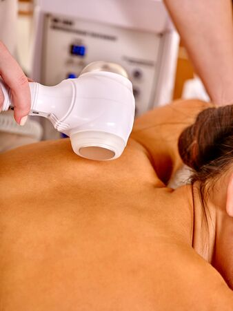 rf: Back of  woman  receiving electric microdermabrasion massage at beauty salon.