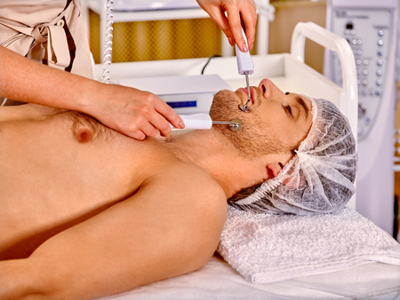 electrophoresis: Man in medical hat receiving electric facial hydradermie treatment at beauty salon.