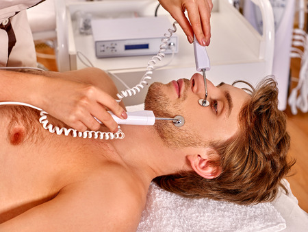 electrophoresis: Man receiving electric galvanization facial hydradermie at beauty salon.