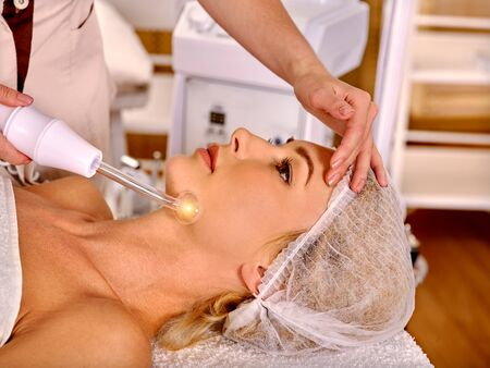 procedures: Young woman in cosmetic hat  receiving darsonvalization  facial treatment at beauty salon.